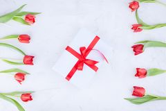 A bouquet of red tulips and a box with a bow on a white background. Surprise and flowers for a romantic holiday. A gift for mom or. Dad royalty free stock photo