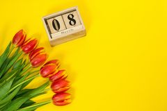 Bouquet of red tulips and cubic wooden calendar with date of 8 march and copy space on bright yellow background. Beggining of stock photo