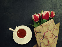 Bouquet of red tulips and cup of tea against a dark background. Festive flower background Stock Photography