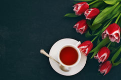 Bouquet of red tulips and cup of tea against a dark background. Festive flower background Royalty Free Stock Photos
