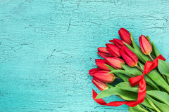 Bouquet of red tulips decorated with red ribbon on blue wooden background Royalty Free Stock Image