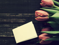 Bouquet of red tulips and and an empty white card for your text Stock Images
