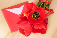 Bouquet of red tulips & envelope on wooden backgound Royalty Free Stock Photos