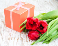Bouquet of  tulips, gift box on a table Stock Photos