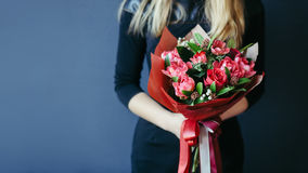 Bouquet of red tulips in girs hands. Unrecognisable. Stock Photos