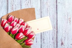 Bouquet of red tulips for the holiday women`s day and valentine`s day on the background of wooden boards.  stock image