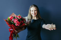 Bouquet of red tulips and surprise woodenbox in girl`s hands. Royalty Free Stock Photos