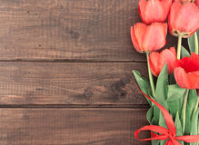 Bouquet of red tulips on wooden background with space for text Stock Photos