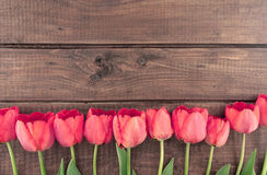 Bouquet of red tulips on wooden background with space for text Royalty Free Stock Photo