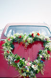Bouquet on a red wedding car. Heart shape bouquet on the rear end of a red wedding car Stock Photos