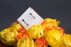 Bouquet of rose flowers and wedding rings in box over grey. Background Stock Image