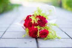 Bouquet rose rouge de fleur ravi avec les feuilles vertes sur le trottoir photo stock