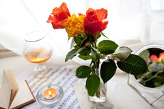 Bouquet of roses. Three beautiful roses with music notes, glass and burning candle Royalty Free Stock Photography