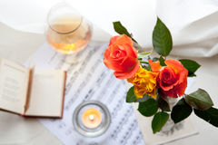 Bouquet of roses. Three beautiful roses with book, music notes and burning candle Stock Photography
