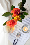 Bouquet of roses. Three beautiful roses with book, music notes and burning candle Royalty Free Stock Image