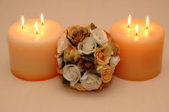 A bouquet of Roses. And two candles on peach colored silk cloth Royalty Free Stock Images