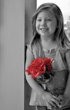 Bouquet Of Roses. Selective colored portrait of a beautiful little girl standing outside against a pillar holding a red bouquet of roses Royalty Free Stock Photography