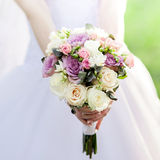 Bouquet of roses in bride's hands. Royalty Free Stock Images
