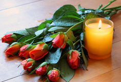 Bouquet of roses, candle. On table made of wood royalty free stock photo
