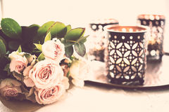 Bouquet of roses and candles. Beautiful bouquet of roses and candles in oriental candlesticks, elegant floral home decorations, vintage filtered Royalty Free Stock Image