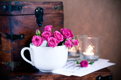 Bouquet of roses in a cup, candles, notes Royalty Free Stock Image
