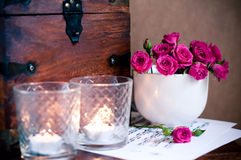 Bouquet of roses in a cup, candles, notes Royalty Free Stock Images