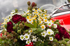 Bouquet of roses, daisies and other wild flowers as wedding decoration on a red vintage car Stock Image