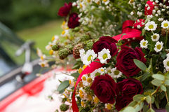 Bouquet of roses, daisies and other wild flowers as wedding decoration on a red vintage car Stock Photo