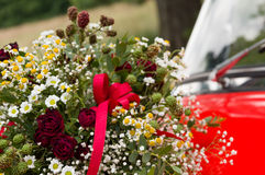 Bouquet of roses, daisies and other wild flowers as wedding decoration on a red vintage car Stock Photography
