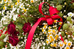 Bouquet of roses, daisies and other wild flowers with a red ribbon Stock Photos