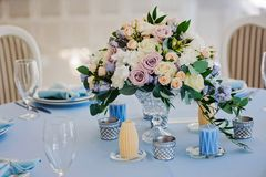 Bouquet of roses delphinium vase glasses cloth. Bouquet in a vase on the table with a tablecloth and candles rose white yellow and blue delphinium glasses plate Stock Photo
