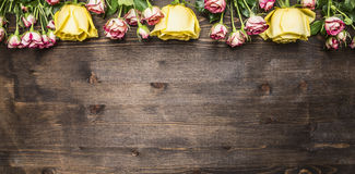 Bouquet of roses of different kinds of flowers, yellow roses and pink shrub roses border ,place text on wooden rustic backgro. Bouquet of roses of different Royalty Free Stock Images
