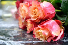 A bouquet of roses in drops of rain. A beautiful bouquet of roses on a table in the rain Stock Photography