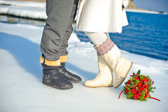 Bouquet of roses and fir cones  legs  bride  groom. Bouquet of roses and fir cones on the ice and legs of bride and groom Royalty Free Stock Images
