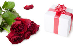 A bouquet of roses and gift on white background. Royalty Free Stock Photos