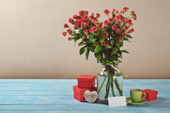 Bouquet of roses, gifts, cup of coffee and card Royalty Free Stock Images