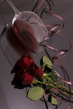 Bouquet of roses and glass red wine on black Stock Photo