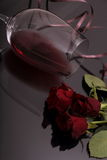 Bouquet of roses and glass red wine on black Royalty Free Stock Photos