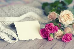 A bouquet of roses on a gray background of tender merino wool and wood. Royalty Free Stock Photo