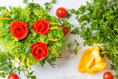 Bouquet of roses made from tomatoes and lettuce, white background. Bouquet of roses made from tomatoes, bell pepper, lettuce on white background Stock Photo