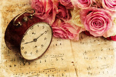 Bouquet of roses on music notes. Vintage textured picture of a bouquet of pink roses and an antique alarm clock on old sheets of music Royalty Free Stock Photo