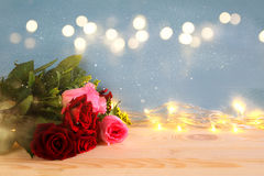 bouquet of roses next to gold garland lights Royalty Free Stock Photo