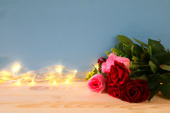 bouquet of roses next to gold garland lights Stock Photos