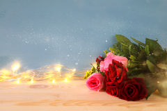 bouquet of roses next to gold garland lights Stock Image