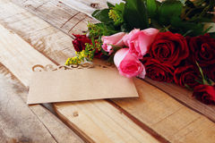 bouquet of roses next to letter on wooden table Stock Photo