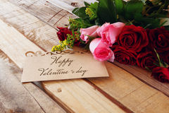 bouquet of roses next to letter on wooden table Royalty Free Stock Images