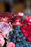 Bouquet of roses, peonies, pomegranates and grapes Royalty Free Stock Images