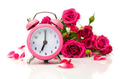 Bouquet of roses and pink alarm clock Royalty Free Stock Photos