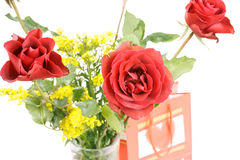 Bouquet of roses with present bag Royalty Free Stock Photo