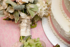 Bouquet of roses and roserie by wedding cake. Royalty Free Stock Images